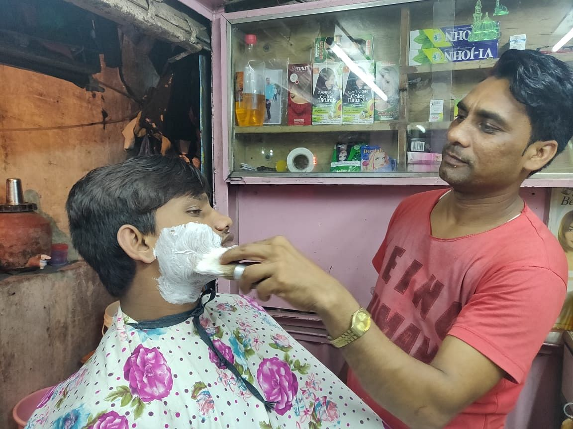 A barber uses Vi-John shaving cream to shave  in Lower Parel. (Source: BloombergQuint)