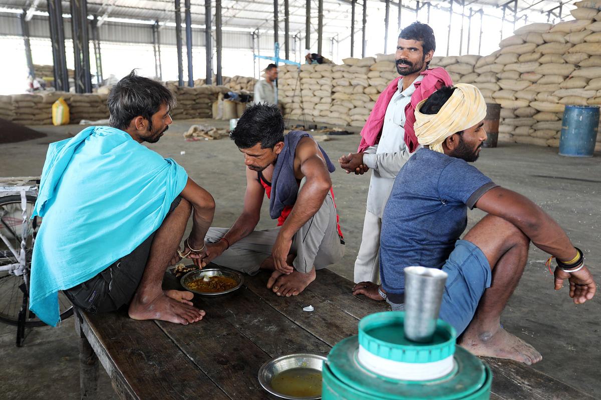 Workers eat at a wholesale grain market in Rewari, Haryana, on May 8, 2019. (Photographer: T. Narayan/Bloomberg)