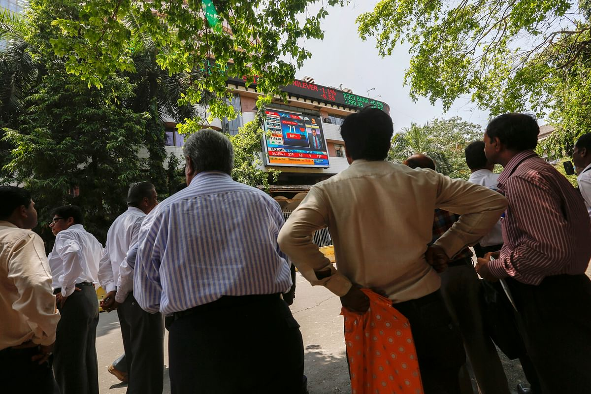 People gather to look up at an electronic screen showing television coverage of the Indian general election at the Bombay Stock Exchange. (Photographer: Vivek Prakash/Bloomberg)