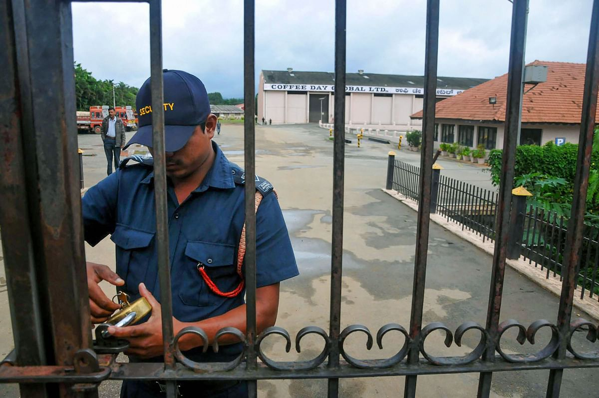 A security guard locks the gate of Coffee Day company after the news of sudden disappearance of Siddhartha (Source: PTI)