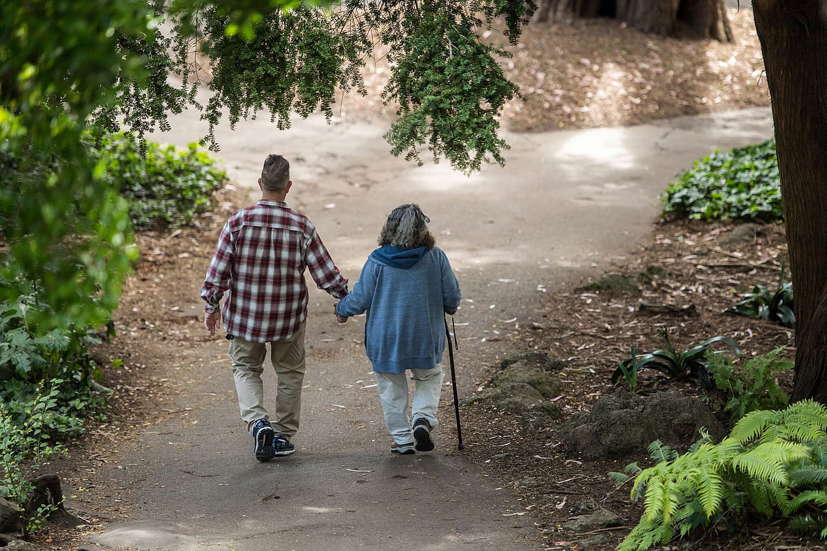 A elderly couple holds hands while walking on a path. (Photographer: David Paul Morris/Bloomberg)