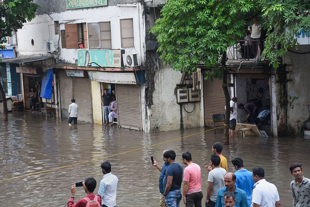 People look on at a waterlogged street where floodwater spilled out of the drainage line following heavy monsoon rainfall, in Surat. (Source: PTI)