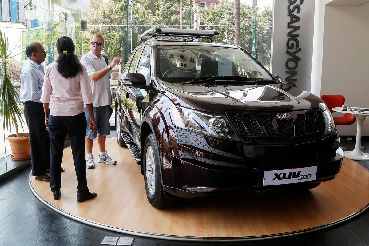 Sales assistants talk to a customer as he looks at a Mahindra XUV500 sports utility on display at a dealership in Mumbai.(Photographer: Vivek Prakash/Bloomberg)