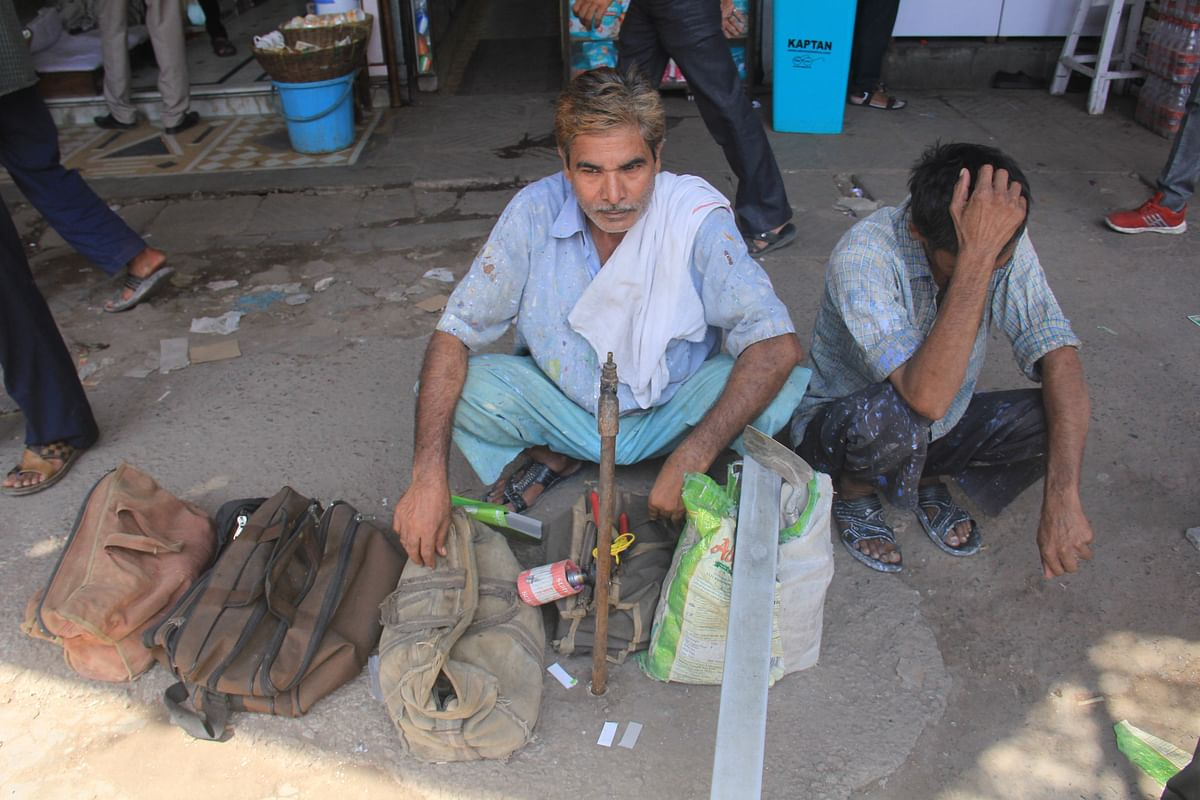 An electrician waits with his assistant and tools by the roadside looking for work near  the Labour Chowk at Sector-49, Noida. (Photographer: Nishant Sharma/BloombergQuint)