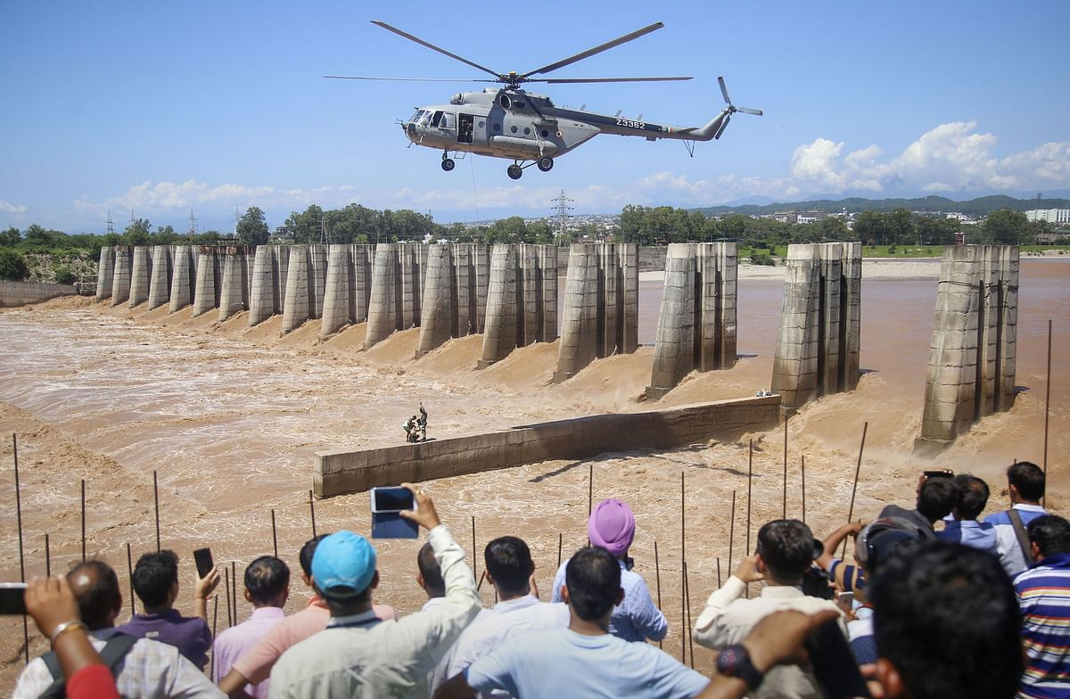 A chopper of the Indian Air Force approaches to airlift two persons stuck on an under-construction bridge at the flooded Tawi river in Jammu (Source: PTI)