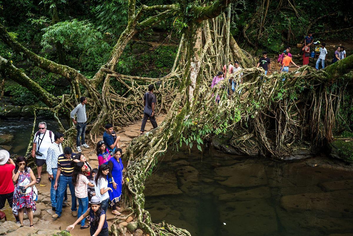 "Tourists cross a bridge known as a ""living root bridge"" in Mawlynnong, Meghalaya, India. (Photographer: Sanjit Das/Bloomberg)"