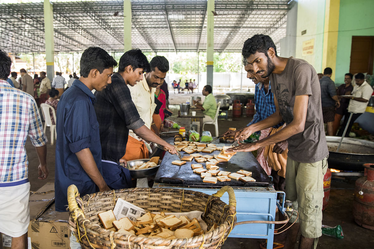 Volunteers prepare and serve food to flood victims at a relief camp. (Photographer: Prashanth Vishwanathan/Bloomberg)