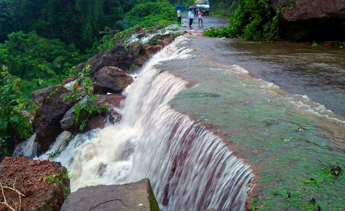 A heavy stream of water gushes down a street following incessant rainfall, causing a landslide, at Chiplun in Ratnagiri, on July 16, 2019. (Photograph: PTI)
