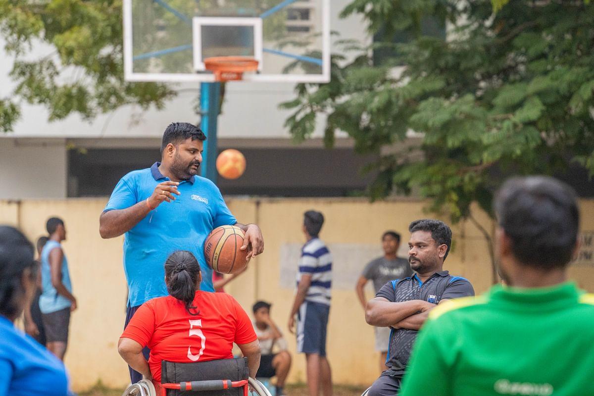 A volunteer  coaching a wheelchair-bound basketball team. (Photograph: Cognizant)