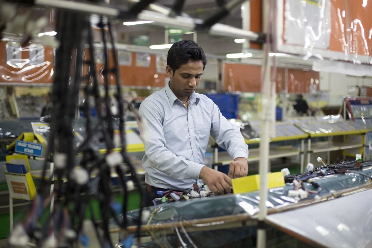 A worker assembles a wire harness at the Motherson Sumi plant in Faridabad. (Photographer: Brent Lewin/Bloomberg)