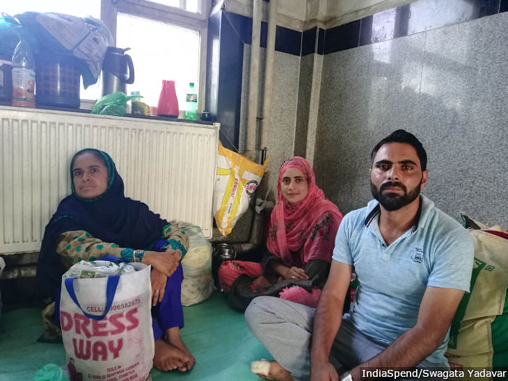"Abdul Qayoom and his wife Shaista sit with a relative in the waiting room of Lal Ded Maternity Hospital, Srinagar. The family lives in Nowgam, 8 km from the hospital, but because of security barriers and dead phones, they prefer to stay in the hospital for two days after discharge than come back for follow-up. ""This 8 km feels like 80 km to us,"" says Qayoom."