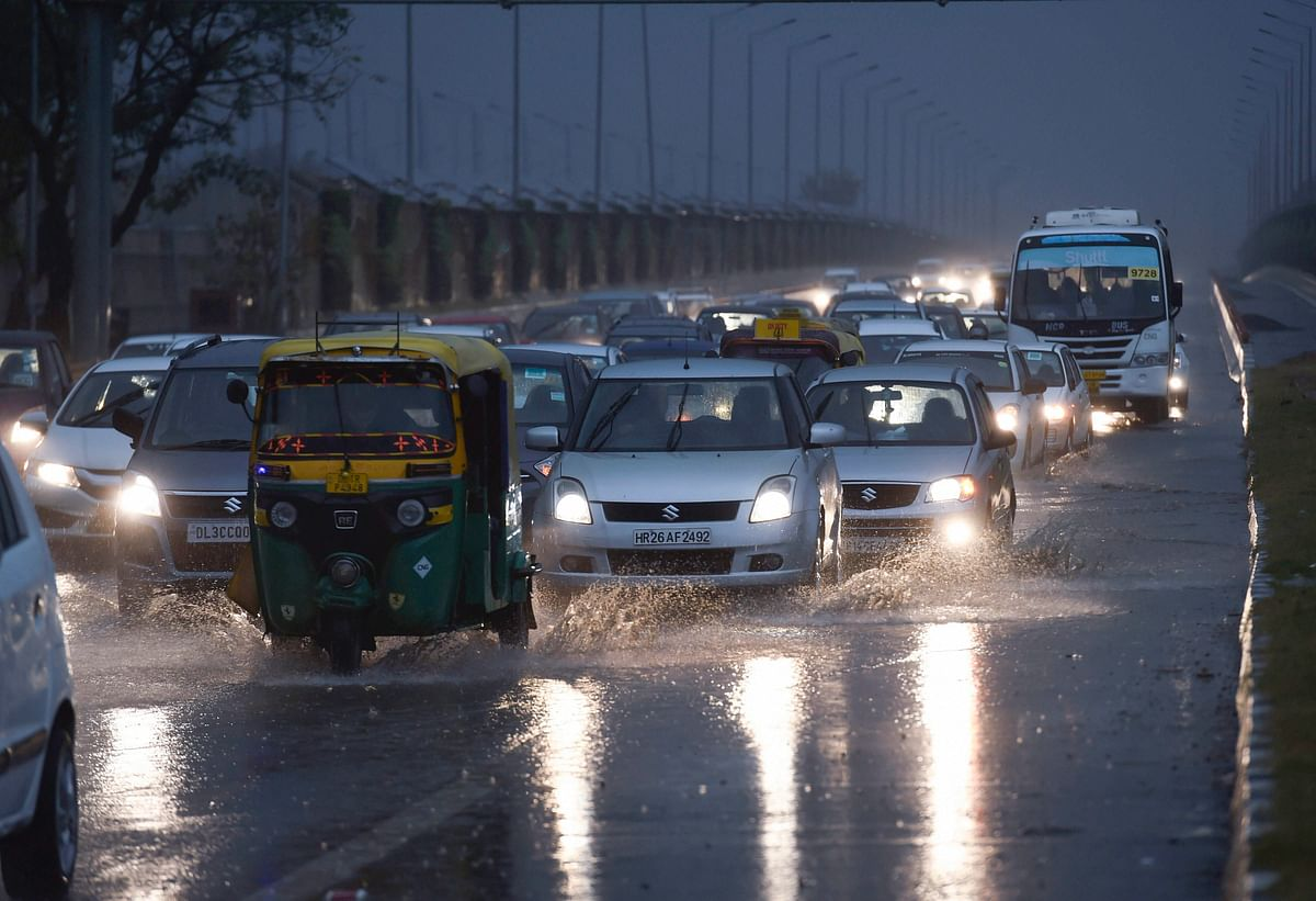 Traffic moves on a street during rains as dark clouds hover over New Delhi. (Photograph: PTI)