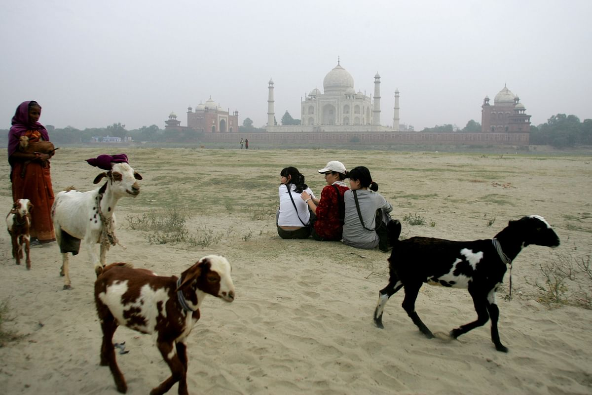 Tourists siting on the banks of the river Yamuna by the Taj Mahal. (Photographer: Sanjit Das/Bloomberg News)