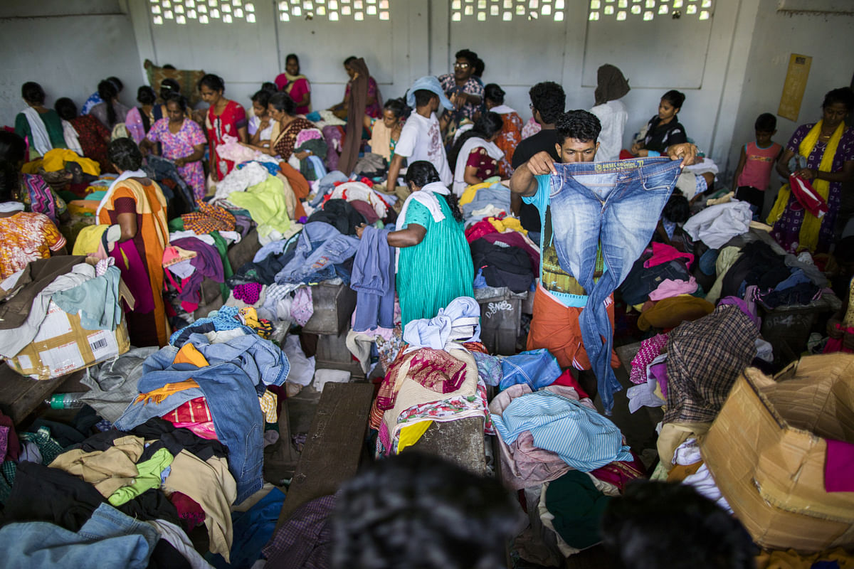 Flood victims look through donated clothing at a relief camp set up in Alappuzha, Kerala. (Photographer: Prashanth Vishwanathan/Bloomberg)