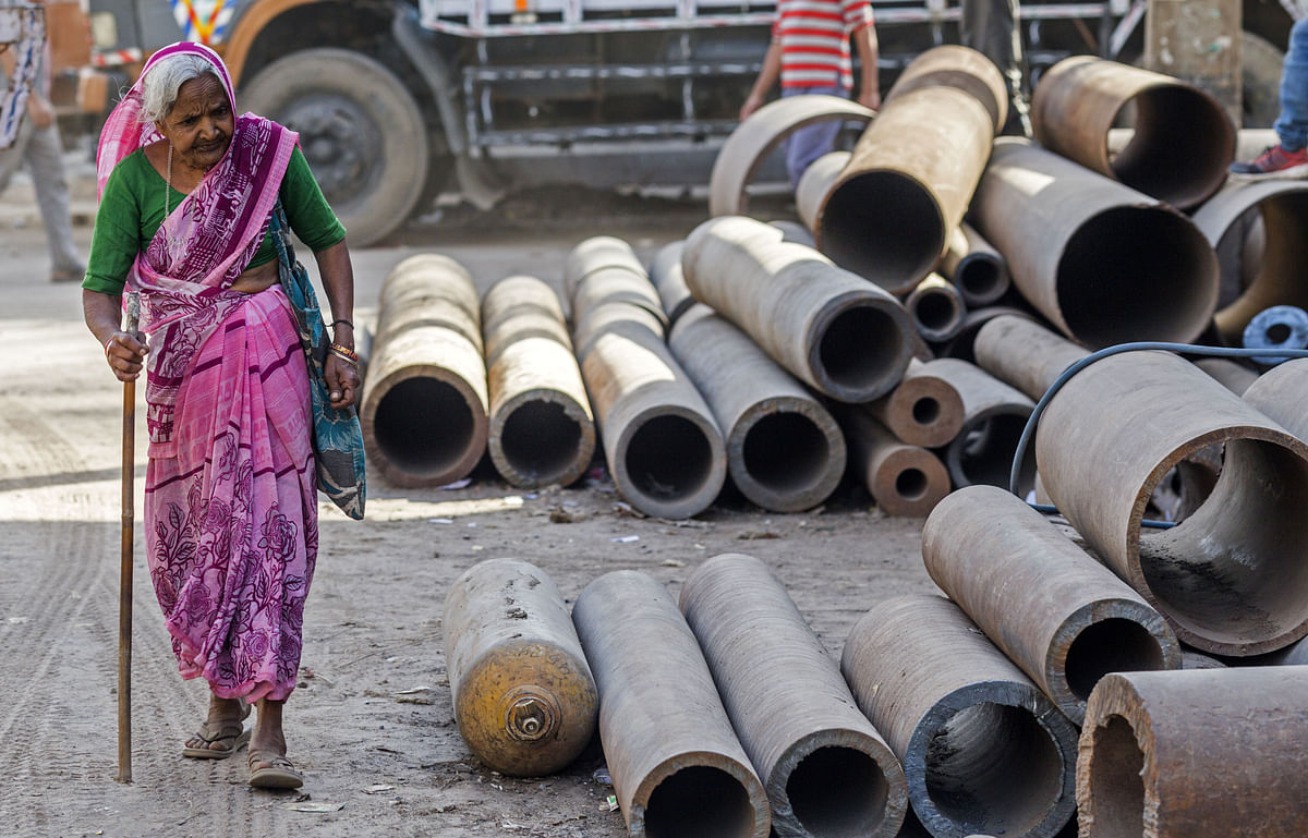 An elderly woman walks past metal pipes on a street in  New Delhi. (Photographer: Prashanth Vishwanathan/Bloomberg)