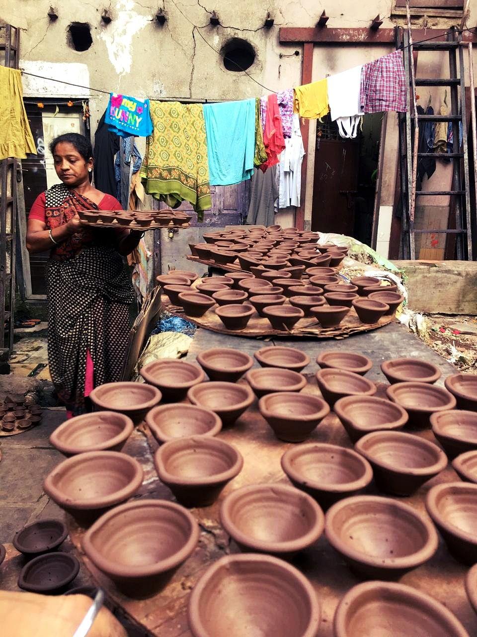 Pramila Parma lays out clay diyas to dry in Dharavi's Kumbharwada. (Source: BloombergQuint)