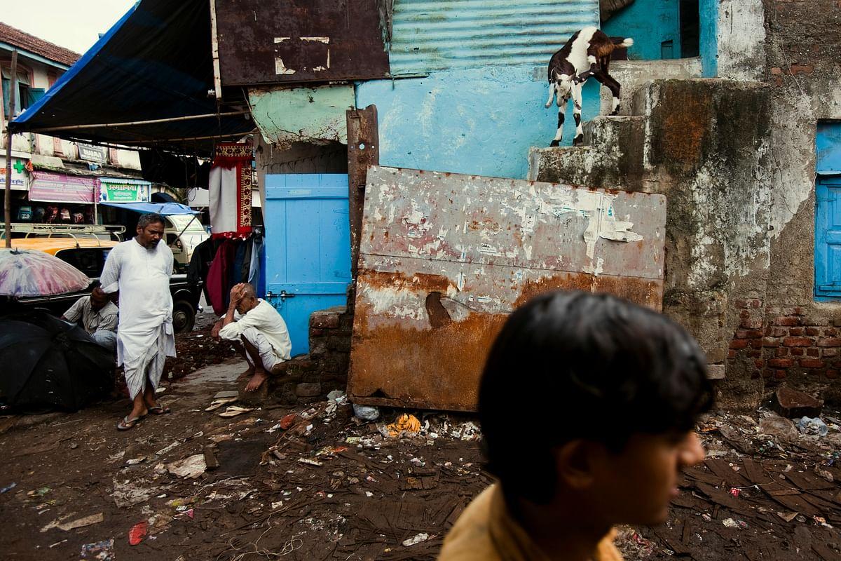 A man passes on a garbage-strewn road in Dharavi, Mumbai. (Photographer: Prashanth Vishwanathan/Bloomberg)