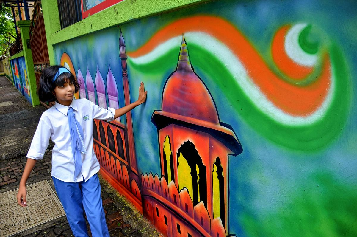 A school student runs her hand on a freshly painted mural on the boundary wall of her school, on Aug. 1, 2019. (Photograph: PTI)
