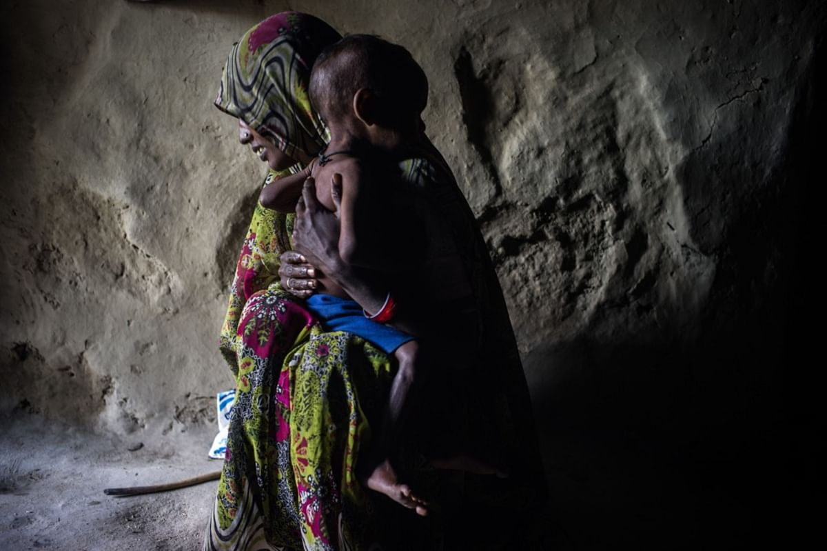 A woman poses for a photograph with her malnourished child  in the village of Paltupur, Uttar Pradesh, India. (Photographer: Sanjit Das/Bloomberg)