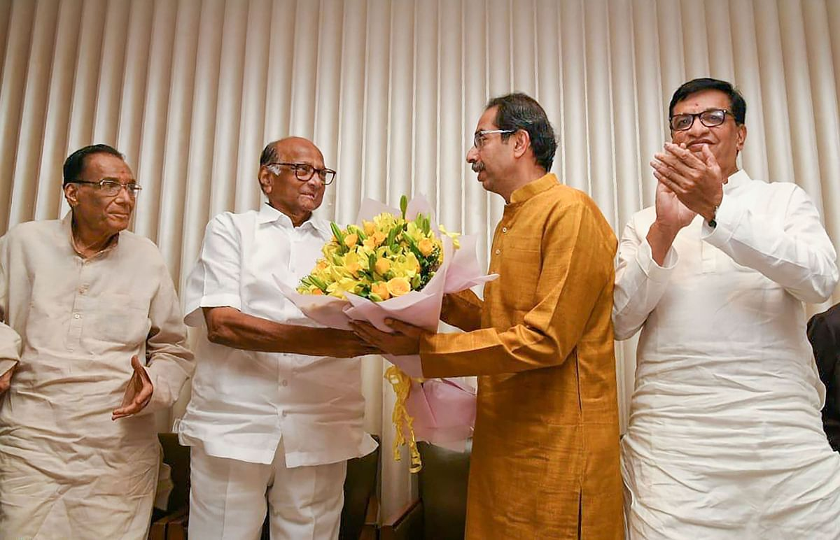 Sharad Pawar presents Uddhav Thackeray a bouquet of flowers. (Source: PTI)