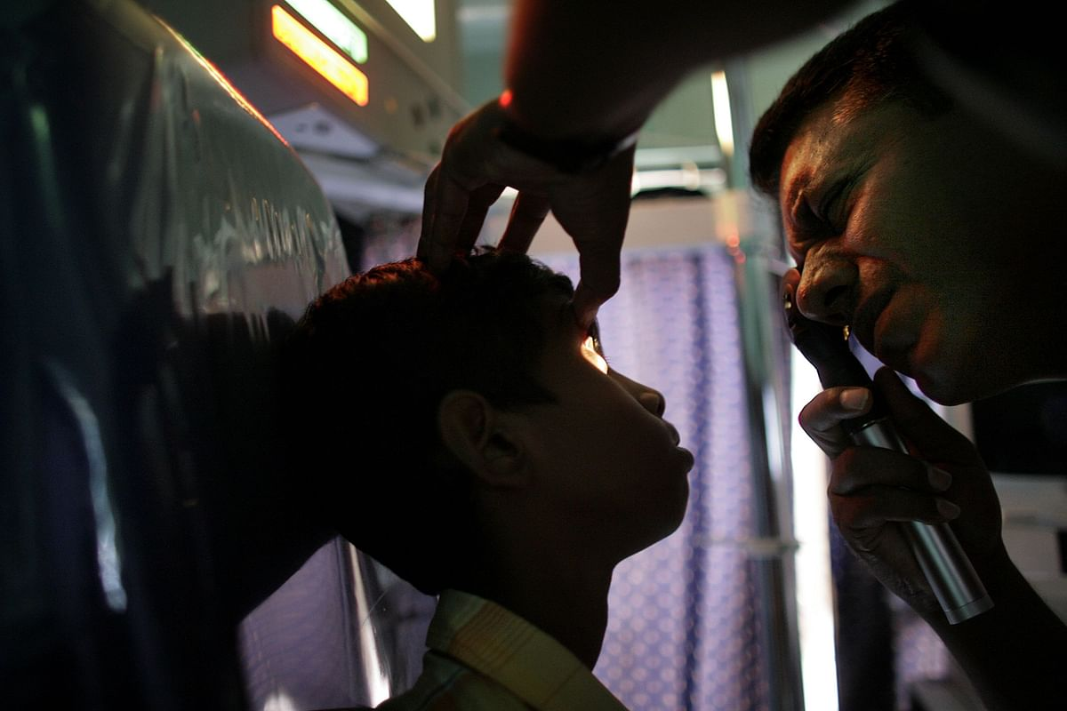 A doctor examines the eyes of a child in Palghar, India. (Photographer: Scott Eells/Bloomberg News)