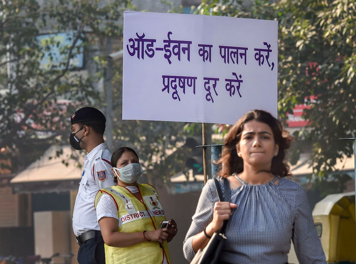 Civil Defence volunteer wearing a mask displays a placard asking people to obey the odd-even rule, in New Delhi (Source: PTI)