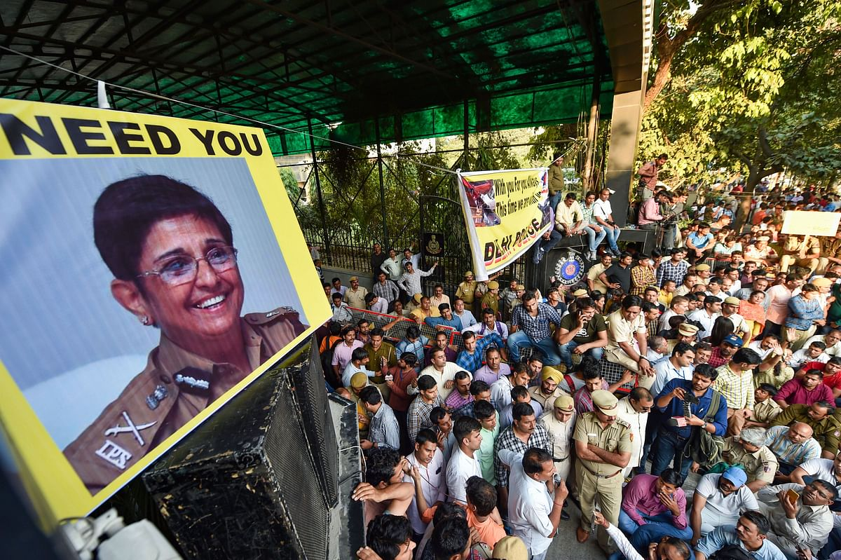 Police personnel display pictures of former IPS officer Kiran Bedi during a protest (Source: PTI)