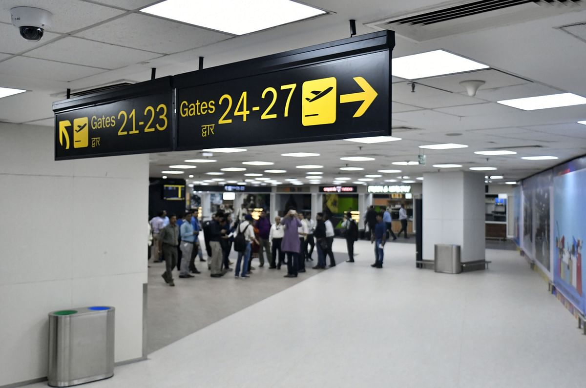 Signs pointing to departure gates hang inside newly inaugurated Terminal 2 building at the Indira Gandhi International Airport in Delhi, India. (Photographer: Anindito Mukherjee/Bloomberg)