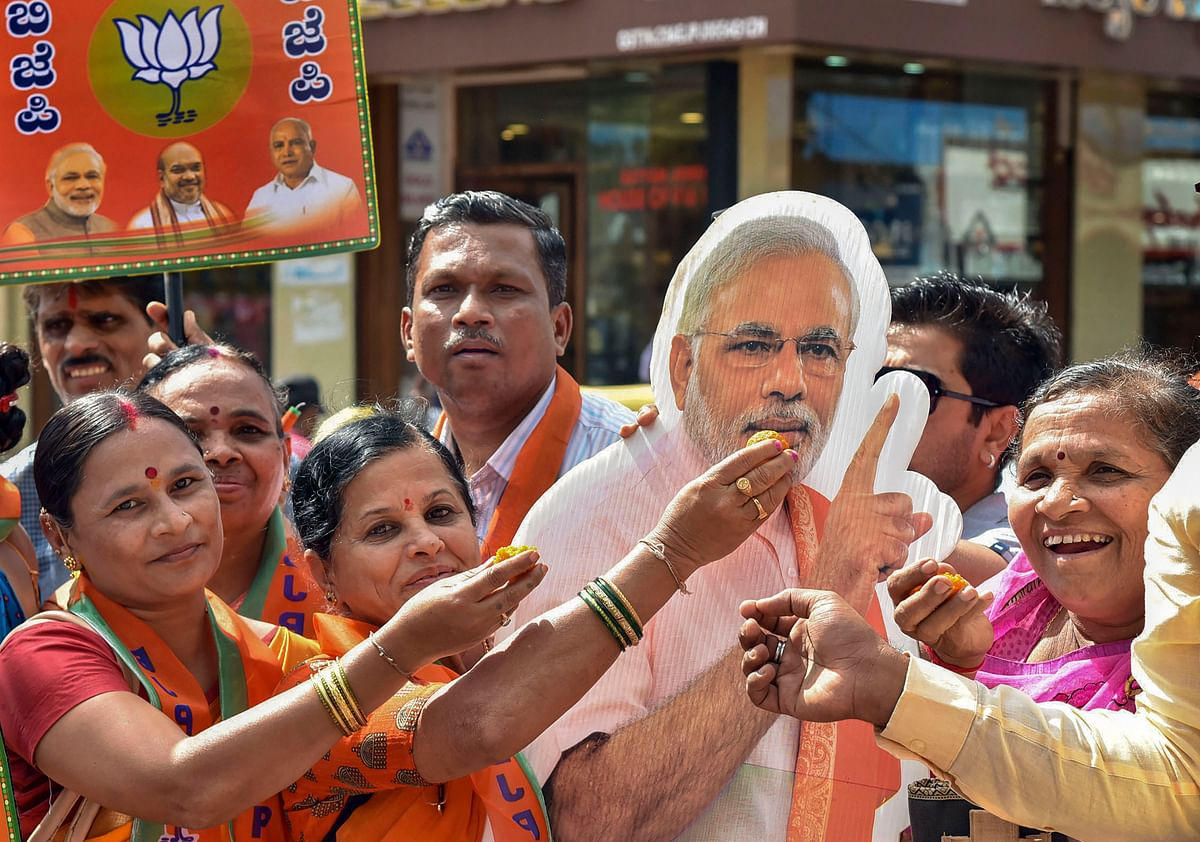 BJP supporters offer sweets to a cut-out of Prime Minister Narendra Modi (Source: PTI)