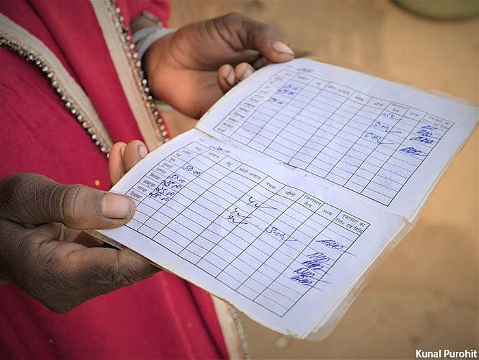 Shakila Bibi, 28, displays her ration card which shows the gaps in supply of rations.