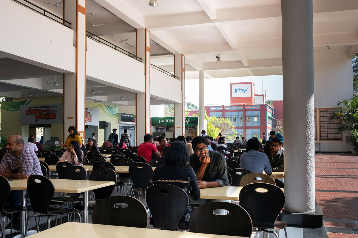 Employees sit at tables in a canteen area at the Infosys campus in Bengaluru, on Jan. 10. 2019. (Photographer: Karen Dias/Bloomberg)