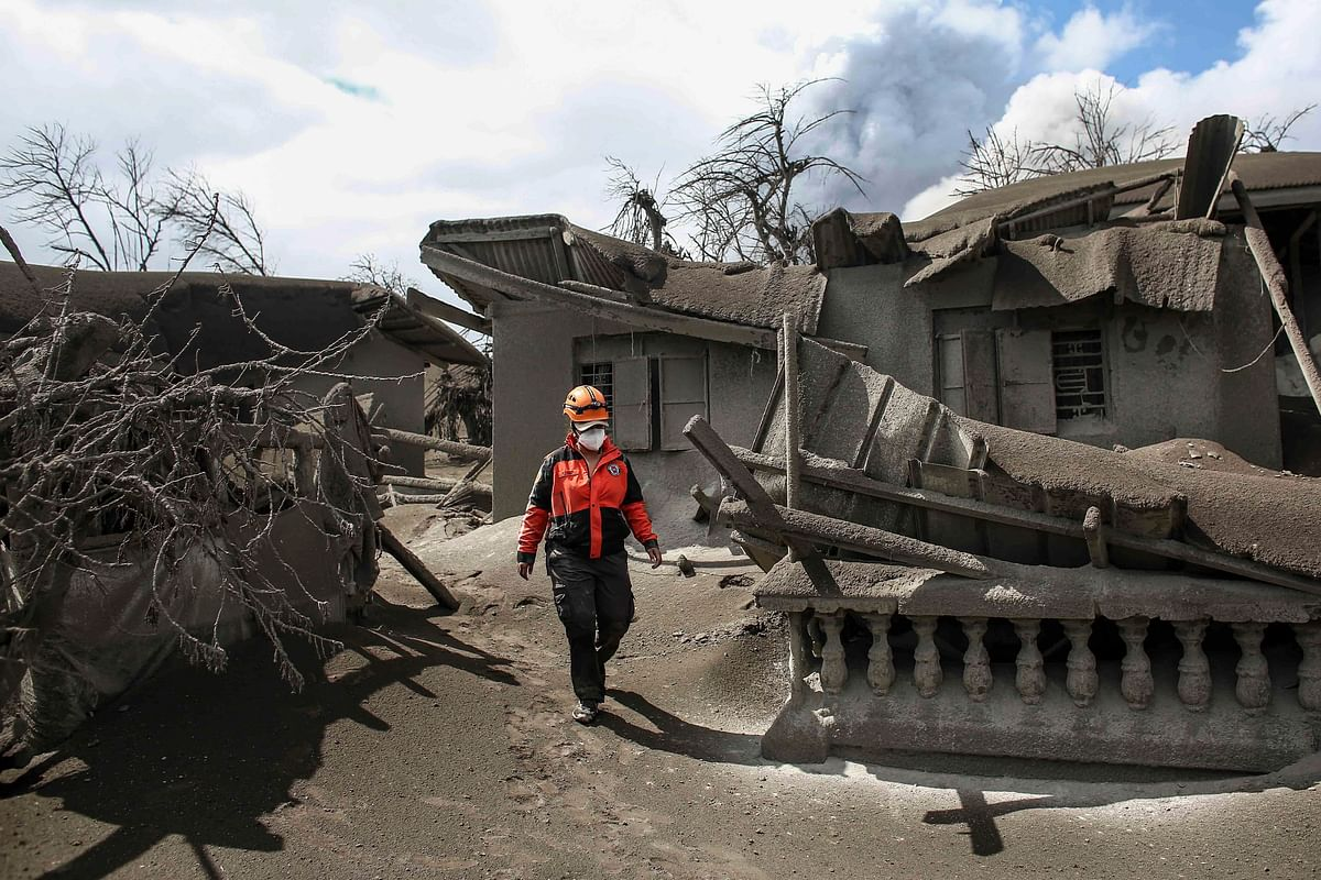 In this Jan. 14, 2020, photo, a rescue volunteer walk on the Taal volcano island beside damaged structures men in Talisay, Batangas province, southern Philippines, as Taal volcano continues to spew ash. The volcano near the Philippine capital spewed lava into the sky and trembled constantly Tuesday, possibly portending a bigger and more dangerous eruption, as tens of thousands of people fled villages darkened and blanketed by heavy ash. (Source: AP Via PTI)