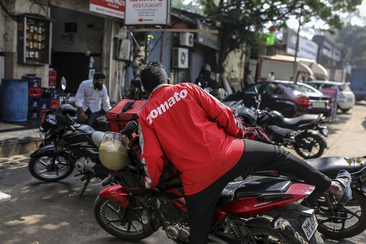 A food delivery rider for Zomato Media Pvt. gets on a motorcycle as he waits for an order outside of a restaurant in Mumbai, India. (Photographer: Dhiraj Singh/Bloomberg)