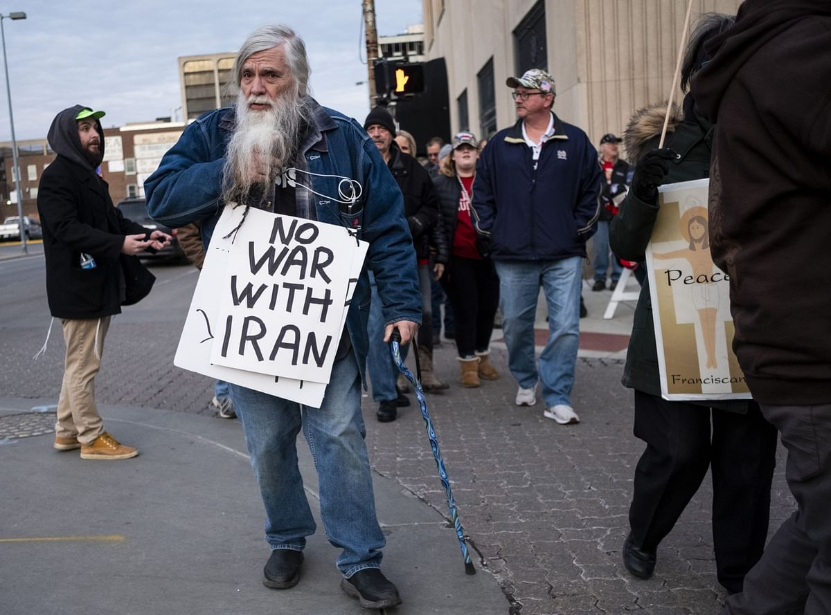 "A demonstrators carries a sign reading ""No War With Iran"" during an anti-war protest in Toledo, Ohio. (Photographer: Matthew Hatcher/Bloomberg)"