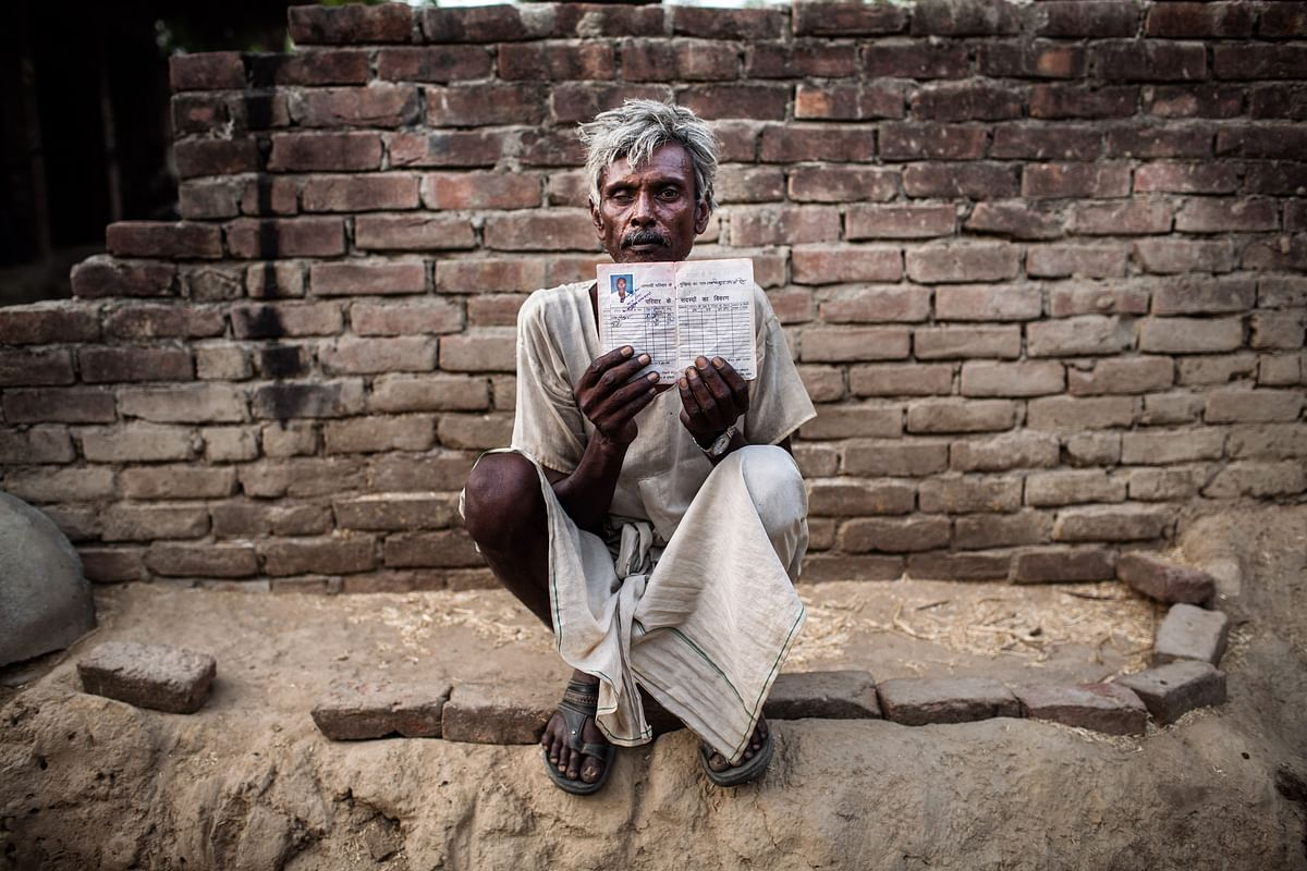 A villager poses for a photo with his government-provided ration card in Sitapur district of Uttar Pradesh. (Photographer: Sanjit Das/Bloomberg)