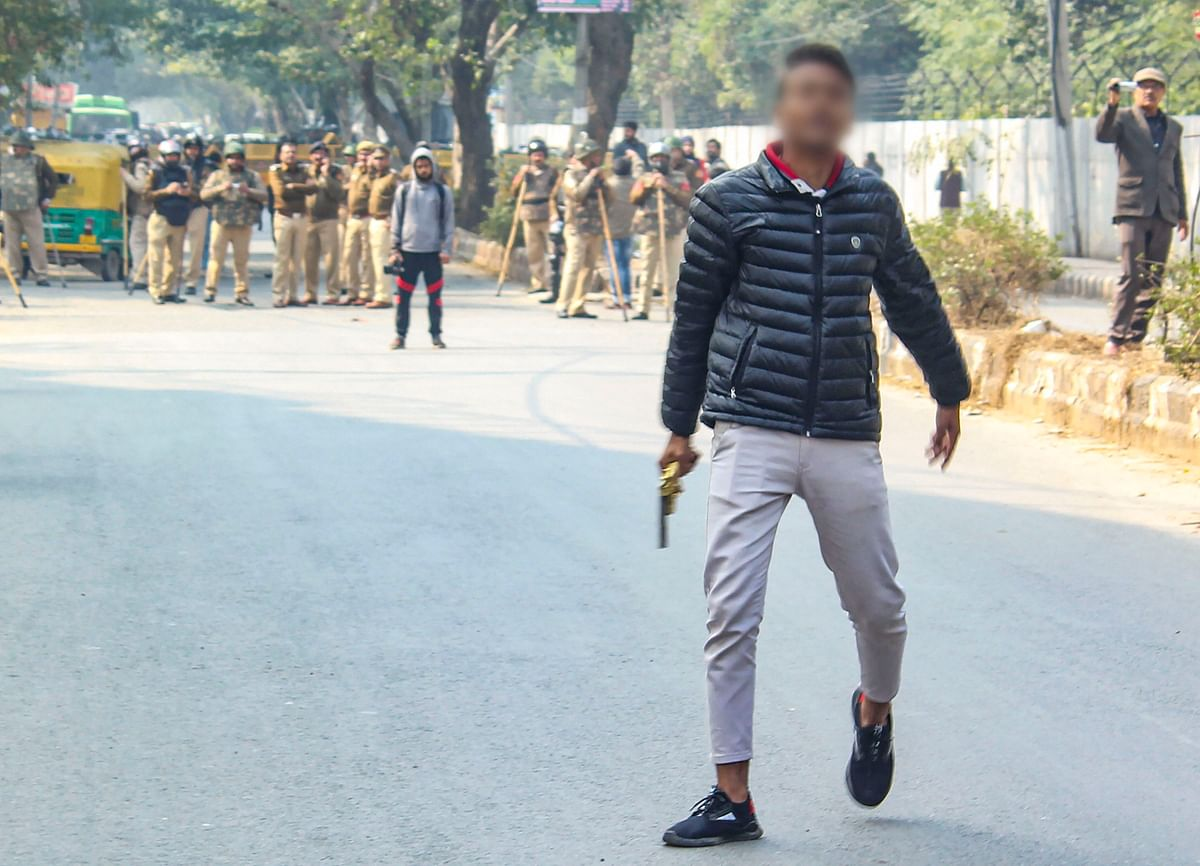 A person (face blurred as his being an adult could not be ascertained), brandishes a gun towards people protesting against the Citizenship Amendment Act, near Jamia Millia Islamia University, in New Delhi, Thursday, Jan. 30, 2020. (Source: PTI)