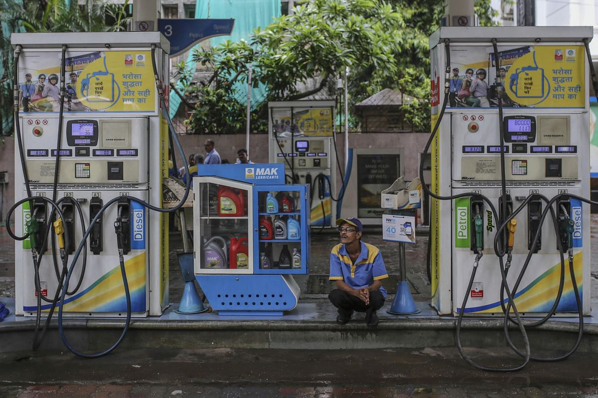 An attendant sits between two fuel pumps at a BPCL fuel station in Mumbai. (Photographer: Dhiraj Singh/Bloomberg)
