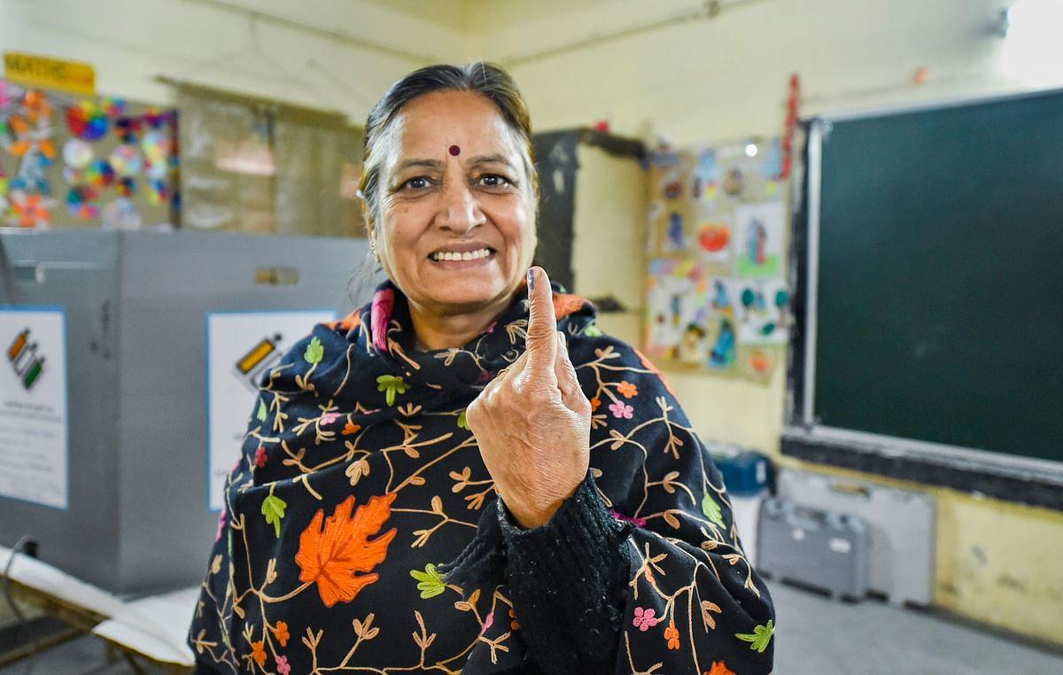 A voter shows her finger marked with indelible ink after casting vote during the Delhi Assembly elections at Old Rajinder Nagar polling station, in New Delhi. (Source: PTI)