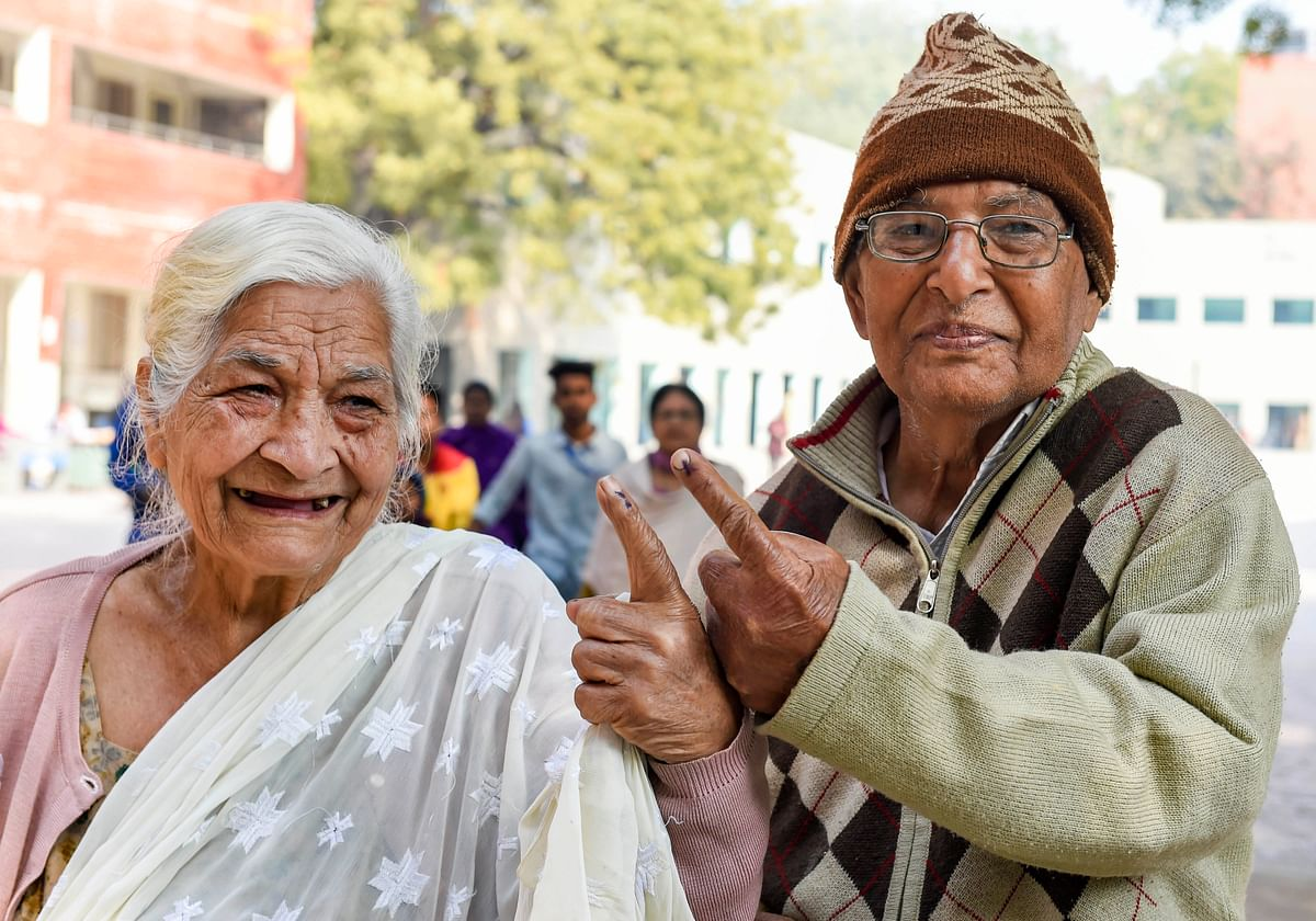 An elderly couple show their inked fingers outside a polling station at CR Park, during Delhi Assembly elections, in New Delhi. (Source: PTI)