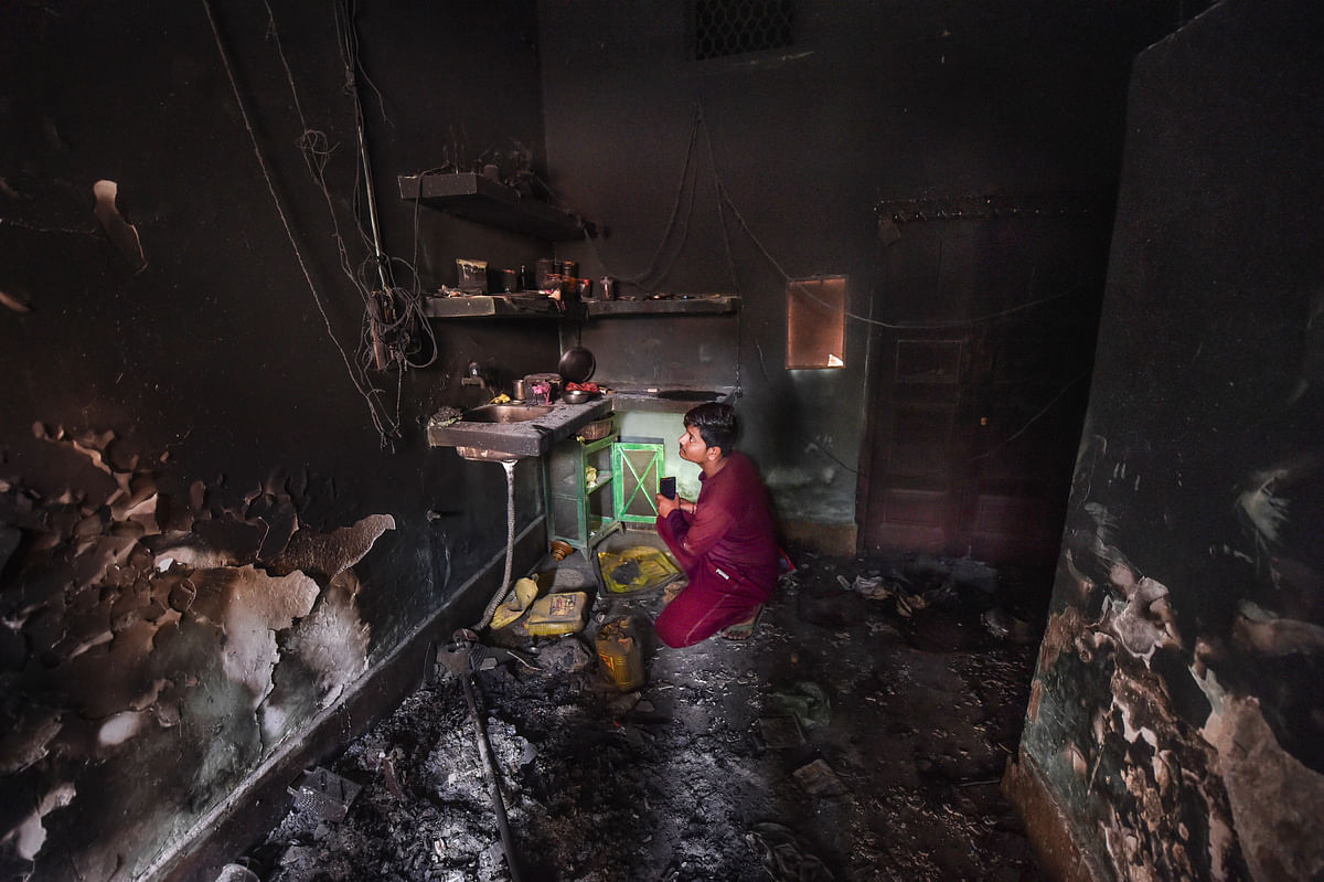 A man inspects a burnt house following riots. (Source: PTI)