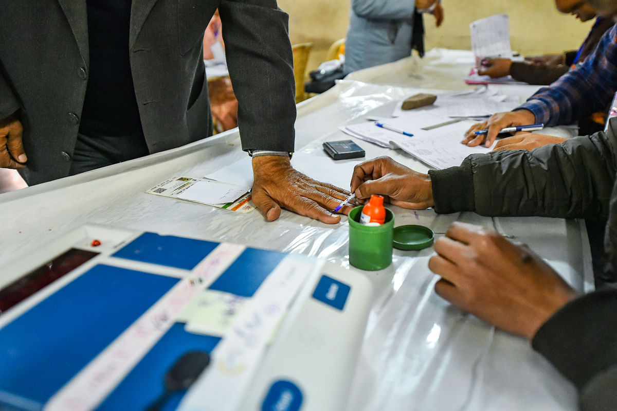 A polling official applies indelible ink on the finger of a voter during the Delhi Assembly elections at Old Rajinder Nagar polling station, in New Delhi. (Source: PTI)
