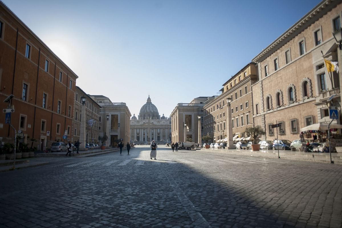 A pedestrian crosses the street, in view of in Saint Peter's Basilica in Vatican State, on Wednesday, March 11, 2020. (Photographer: Geraldine Hope Ghelli/Bloomberg)