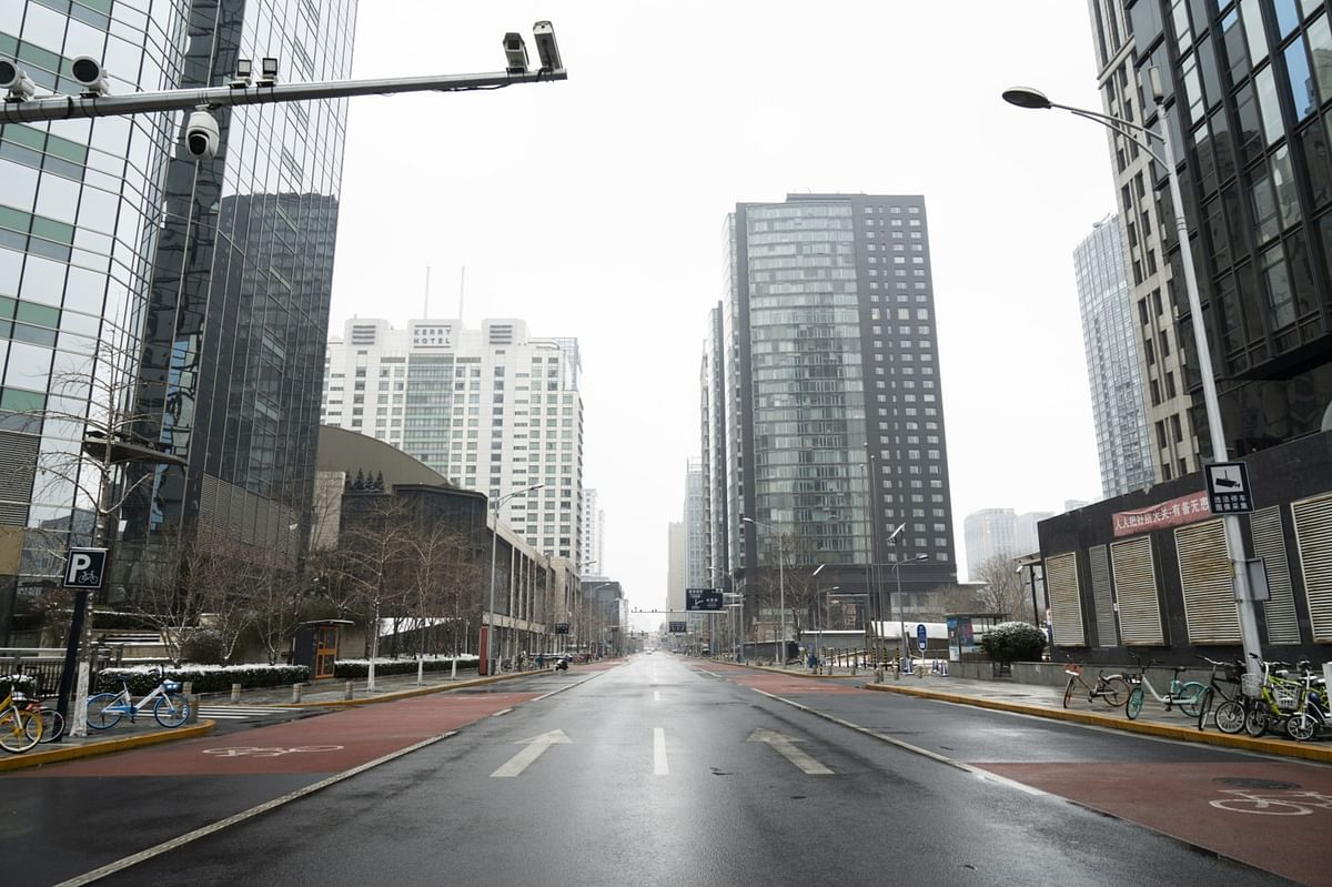 Commercial buildings stand along a deserted road in Beijing, China, on Sunday, Feb. 2, 2020. (Photographer: Giulia Marchi/Bloomberg)
