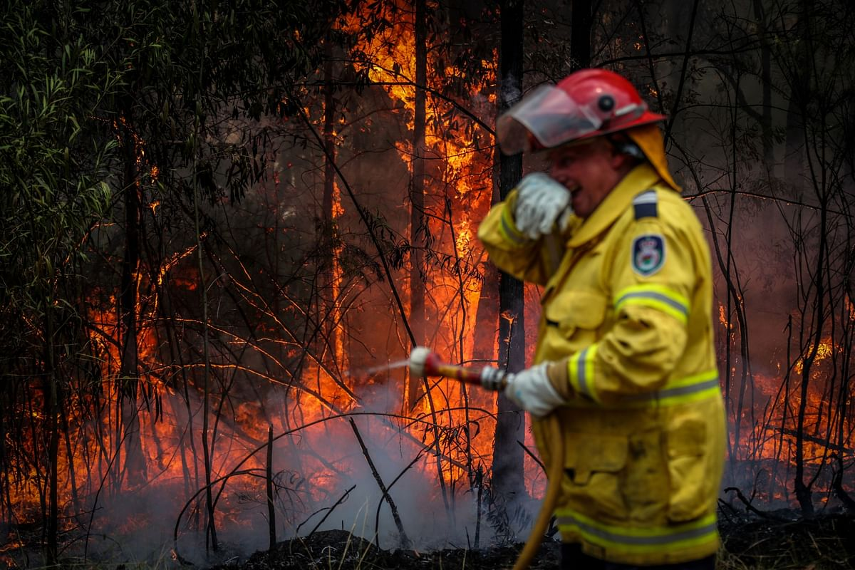 A volunteer dousing a fire in New South Wales, Australia. (Photographer: David Gray/Bloomberg)