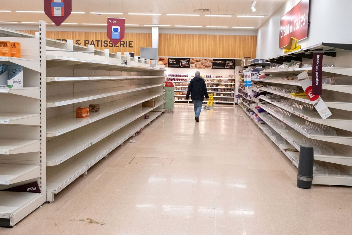 A customer walks past empty shelves after sugar, flour, bread and cakes products sold out in a J Sainsbury Plc supermarket in London, U.K., on Tuesday, March 17, 2020. (Photographer: Bryn Colton/Bloomberg)