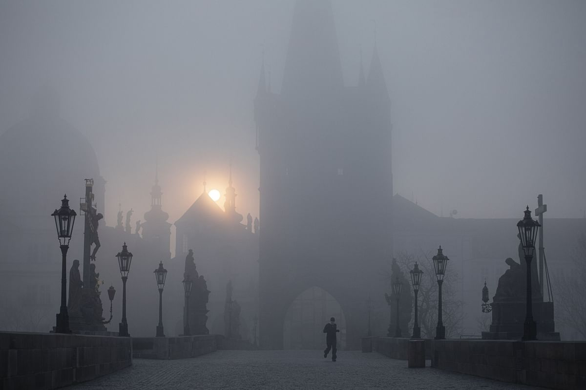 A runner jogs over an empty Charles Bridge at dawn in Prague, Czech Republic, on Wednesday, March 18, 2020. (Photographer: Milan Jaros/Bloomberg)