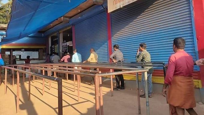 People line up outside alcohol store in Kerala.