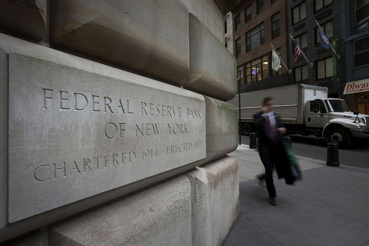 Pedestrians walk past the New York Federal Reserve building in New York. (Photographer: Scott Eells/Bloomberg)