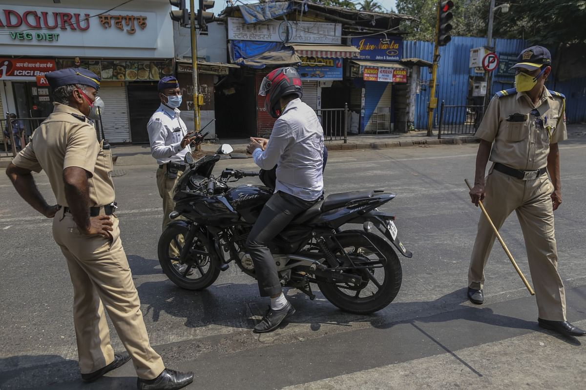 Police officers wearing protective face masks stop motorcyclist during a curfew in Mumbai, India. (Photographer: Dhiraj Singh/Bloomberg)