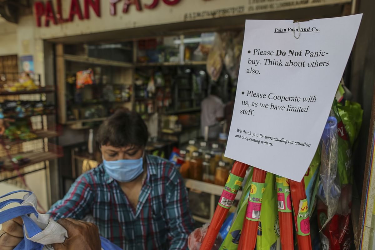 A sign advises customers not to panic buy goods outside grocery store in Mumbai, India, on Wednesday, March 25, 2020. (Photographer: Dhiraj Singh/Bloomberg)
